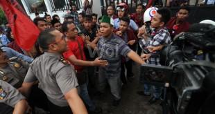 Petugas polisi mengahalau pengunjukrasa yang tergabung dalam Masyarakat Pribumi Indonesia saat berunjukrasa dengan membakar ban dan memblokir jalan di depan kantor Walikota Medan, Jumat (10/4). Mereka menuntut agar pemerintah turun tangan mengembalikan Mesjid Al Hidayah di Jalan Madura yang telah di bongkar oleh pengembang. (WOL Photo/Ega Ibra)