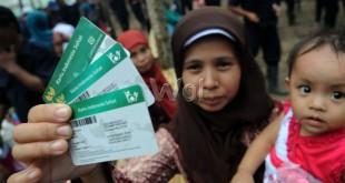 Warga menunjukan Kartu Indonesia Sehat (KIS) usai pembagian oleh Presiden RI Joko Widodo di Desa Sei Karang, Deli Serdang, Sumatera Utara, Sabtu (18/4). Sebanyak 516 kepala keluarga yang juga pekerja di PTPN III menerima KIS. (WOL Photo/Ega Ibra)