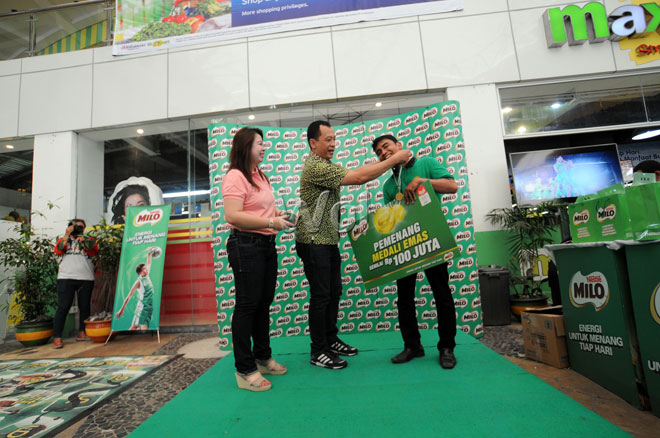 Regional Sales Manager Sumatera Nestle Indonesia Syuhada Rosyidi (tengah) menyerahkan medali emas kepada Tajri Abdillah (kanan) sebagai pemenang undian MILO Gold Medal tahap IV di Medan, Minggu (14/6). Milo menyediakan delapan buah medali emas yang akan diundi setiap minggu selama periode Mei hingga Juni 2015. (WOL Photo Ega Ibra)