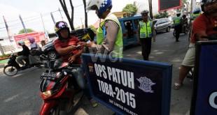 Petugas kepolisian memeriksa surat-surat pengendara yang melintas saat operasi patuh toba 2015 di Jalan Sisingamangaraja, Medan, Rabu (3/6).  Razia perdana operasi patuh toba 2015 bertujuan untuk mengurangi angka kecelakaan lalu lintas terhadap pengendara di jalanan. (WOL Photo/Ega Ibra)