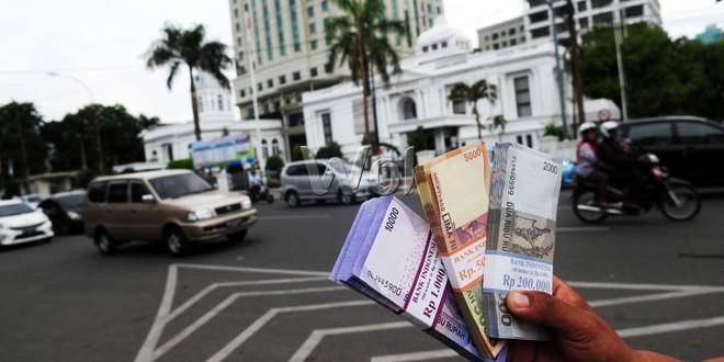 Seorang penyedia jasa penukaran uang menawarkan uang receh miliknya kepada pengendara yang melintas di sekitar Lapangan Merdeka, Medan, Rabu (8/7). Mereka mengambil untung 10 persen dari setiap nominal uang yang ditukarkan. (WOL Photo/Ega Ibra)