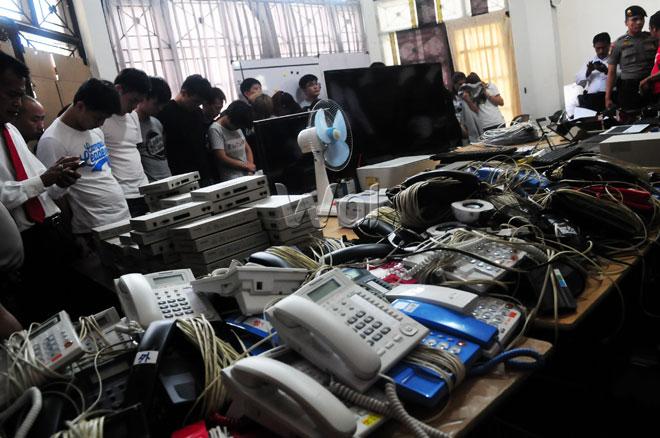 Petugas kepolisian mengamankan puluhan Warga Negara Asing (WNA) saat penggerebekan jaringan cyber crime di Komplek Perumahan Taman Setia Budi Indah, Medan, Senin (27/7). Selain para WNA petugas juga mengamankan barang bukti lain seperti tujuh buah laptop, dua unit televisi, 10 unit HT, 54 unit telepon kabel, dua unit printer, 65 unit handphone, 27 paspor, 12 unit keyboard, dua unit modem dan sejumlah mata uang asing yang diduga digunakan untuk melakukan tindak kejahatan cyber crime secara internasional di wilayah Indonesia. (WOL Photo/Ega Ibra)