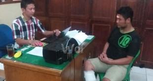 Penyidik Reskrim Polsek Medan Baru, Aiptu Edi Supratman SH sedang melakukan pemeriksaan terhadapa tersangka HS, begal yang kena tembak/WOL Photo/Gacok