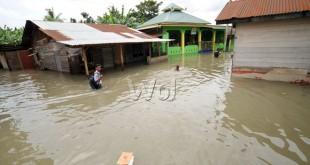 Seorang pelajar berjalan melintasi banjir yang merendam rumah warga di kawasan Jalan Rawe, Kecamatan Medan Labuhan, Martubung, Medan, Senin (30/11). Hujan deras yang mengguyur kota Medan dan sekitarnya sejak dini hari tadi, mengakibatkan sejumlah pemukiman warga dan sekolah terendam banjir. (WOL Photo/Ega Ibra)
