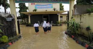 Sejumlah murid SMP Negeri 10 memasuki sekolahnya yang terendam banjir, Medan, Rabu (25/11). Selain menghentikan aktifitas belajar mengajar, banjir juga mengganggu peringatan Hari Guru 25 November. (WOL Photo/Ega Ibra)