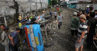 Warga melihat mobil angkot yang ditabrak oleh kereta api di perlintasan rel kereta api Jalan Sisingamangaraja, Medan, Rabu (25/11). Sebanyak sepuluh orang penumpang angkot mengalami luka-luka dalam kecelakaan tersebut. (WOL Photo/Ega Ibra)