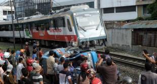 Warga melihat mobil angkot yang ditabrak oleh kereta api di perlintasan rel kereta api Jalan Sisingamangaraja, Medan, Rabu (25/11). Sedikitnya belasan orang penumpang angkot mengalami luka-luka dalam kecelakaan tersebut. (WOL Photo/Ega Ibra)