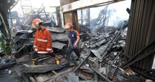 Petugas pemadam kebakaran melintas di antara puing sisa kebakaran rumah usaha di Jalan Gatot Subroto, Medan, Kamis (12/5). Kebakaran menghanguskan enam unit bangunan semi permanen. (WOL Photo/Ega Ibra)