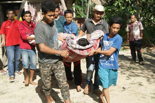 Warga dan Tim Ikatan Pekerja Sosial Masyarakat (IPSM) Kecamatan Langkahan, membawa mursalin ke ambulance yang telah disiapkan. (WOL Photo/Chairul Sya'ban).