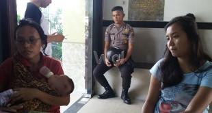 Tika Br Sitanggang sambil menggendong bayinya, mengadukan suaminya ke Polsek Medan Sunggal. (WOL Photo/Gacok)