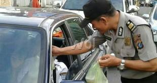 Kanit Sabhara Polsek Medan Baru AKP Maju Harahap SH memberikan takjil buka puasa kepada pengemudi di Jalan S. Parman Medan. (WOL Photo/ucok)