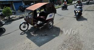 Sejumlah kendaraan melintasi jalan yang berlubang di kawasan Jalan Krakatau Medan, Jumat (1/7). Minimnya perhatian Pemerintah Kota Medan untuk melakukan perbaikan dapat membahayakan pengendara terutama sepeda motor saat melintasi jalan tersebut. (WOL Photo/Ega Ibra)