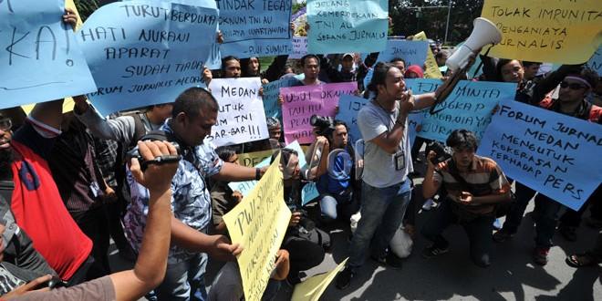 "Wartawan Kota Medan memegang spanduk dan berorasi saat menggelar unjuk rasa "" menolak Kekerasan Terhadap Jurnalis"" di Medan, Selasa (16/8). Aksi itu mengecam tindakan kekerasan yang dilakukan oknum anggota TNI AU kepada dua orang wartawan Medan saat bertugas dan meminta pihak terkait untuk mengusut tuntas kasus tersebut. (WOL Photo/Ega Ibra)"