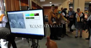 Petugas haji memeriksa suhu tubuh Jamaah Haji saat tiba di Asrama Haji Medan, Selasa (20/9). Pemeriksaan dilakukan untuk melihat kesehatan Jamaah Haji melalui suhu tubuh dan mengantisipasi masuknya virus MERS-CoV usai menunaikan ibadah haji. (WOL Photo/Ega Ibra)