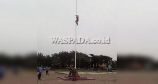 Petugas manjat tiang bendera perbaiki tali pengait sebelum upacara Hari Sumpah Pemuda dimulai. (WOL Photo/Chairul Sya'ban)
