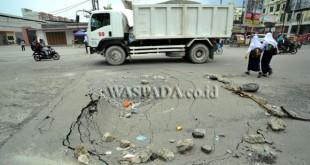 Truk melintas di jalan yang berlubang di kawasan Jalan William Iskandar Pasar V, Medan, Selasa (25/10). Banyaknya truk yang melintas dengan beban berlebih diduga menjadi penyebab rusaknya jalan tersebut. (WOL Photo/Ega Ibra)