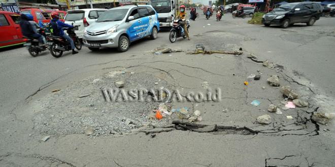 Sejumlah pengendara menghindari lubang di kawasan Jalan William Iskandar Pasar V, Medan, Selasa (25/10). Banyaknya truk yang melintas dengan beban berlebih diduga menjadi penyebab rusaknya jalan tersebut. (WOL Photo/Ega Ibra)