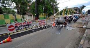 Sejumlah kendaraan melintas di dekat proyek galian kabel PLN di kawasan Jalan Palang Merah Medan, Kamis (20/10). Proyek tersebut merupakan pekerjaan galian kabel PLN 150 kv. (WOL Photo/Ega Ibra)