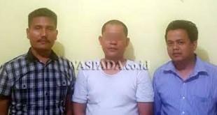 Panit II Reskrim Polsek Medan Sunggal, Ipda Martua Manik SH MH (kiri) didampingi penyidik pembantu mengapit tersangka. (WOL Photo/Gacok)