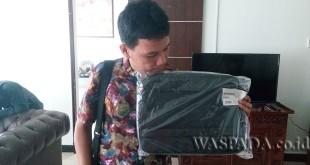 Salah seorang awak media tengah menunjukkan tas laptop merek Lenovo M4180 yang masih tersisa, Selasa (17/1).