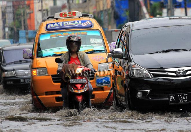 Kendaraan bermotor melaju melintasi genangan air di kawasan Jalan Thamrin, Medan, Selasa (14/2). Hujan terus menerus sepanjang hari dan buruknya drainase di kawasan tersebut mengakibatkan genangan air hingga setinggi 15 cm pada badan jalan. (WOL Photo/Ega Ibra)
