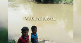 Dua bocah berdiri di pinggir Sungai Belawan kawasan Tunggul Itam (TI).(WOL. Photo/gacok).