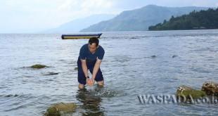 Bupati Simalungun JR Saragih memastikan kondisi air di Danau Toba, dengan turun langsung ke air di Danau Toba maka sekaligus menepis isu hadirnya biota air di Danau Toba, Rabu (22/2). (WOL Photo)