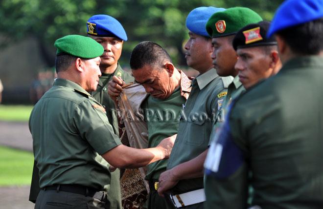 Kasdam I/Bukit Barisan Brigjen TNI Tiopan Aritonang (kiri) menanggalkan seragam anggota TNI pada upacara pemberhentian tidak dengan hormat (PTDH), di Medan, Jumat (17/2). Sebanyak 21 prajurit TNI Kodam I/Bukit Barisan dipecat, diantaranya terlibat narkoba dan desersi. (WOL Photo/Ega Ibra)