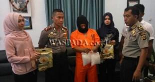 Tersangka MS pakai sebo, diintrogasi Kapolres Aceh Utara, AKBP Untung Sangaji, didampingi dua polwan.(foto chairul sya'ban).