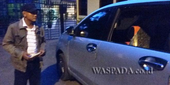 Seorang warga, Rahmat Karo-karo SH sedang melihat kaca mobil yang dipecahkan pelaku kejahatan, tas berisikan surat berharga dan laimnya hilang dilarikan pencuri. (WOL Photo/Gacok)
