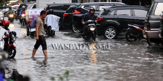 Pejalan kaki melintasi banjir yang menggenangi kawasan Jalan Perniagaan, Medan, Rabu (19/4). Buruknya sistem drainase menyebabkan kawasan tersebut menjadi daerah langganan banjir hingga ketingian 15 cm saat hujan turun. (WOL Photo/Ega Ibra)