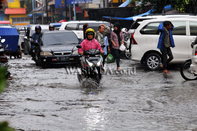Sejumlah pengendara melintasi banjir yang menggenangi kawasan Jalan Perniagaan, Medan, Rabu (19/4). Buruknya sistem drainase menyebabkan kawasan tersebut menjadi daerah langganan banjir hingga ketinggian 15 cm saat hujan turun. (WOL Photo/Ega Ibra)