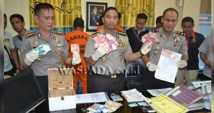 Ketua Tim Saber Pungli Polda Aceh, Kombes Pol Darmawan Sutawijaya (tengah) Menunjukkan Barang Bukti Pungli di Lhokseumawe. (WOL Photo/Chairul Sya'ban)