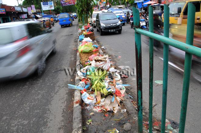 Kendaraan melintas di dekat tumpukan sampah yang berada di median jalan, Kawasan Pasar Sei Sikambing, Medan, Rabu (26/4). Berbagai sampah sisa dagangan menumpuk di median jalan sehingga menimbulkan bau tak sedap serta mengganggu arus lalu lintas. (WOL Photo/Ega Ibra)