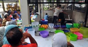 Warga mengantre pembagian bubur sup di halaman Masjid Raya, Medan, Senin (29/5). Setiap harinya selama bulan Ramadhan pengurus masjid menyediakan sekitar 900 porsi bubur yang dibagikan secara gratis kepada masyarakat untuk menu berbuka puasa. (WOL Photo/Ega Ibra)