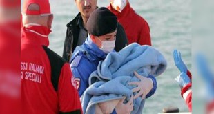 Dokumen foto seorang polisi Italia menolong bayi pengungsi yang menaiki kapal kecil dari Libya menuju perairan Italia. (ANSA)