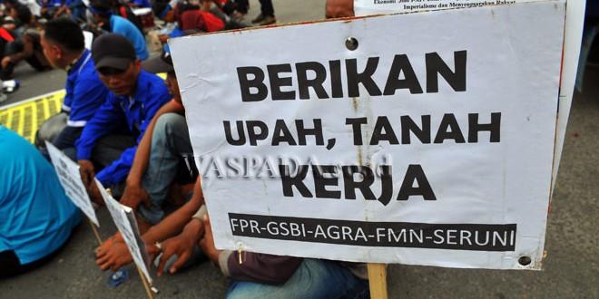 Buruh peserta aksi memegang spanduk tuntutan saat aksi Hari Buruh Internasional, di Medan, Senin (1/5). Dalam aksinya mereka meminta pemerintah meningkatkan kesejahteraan para kaum buruh. (WOL Photo/Ega Ibra).
