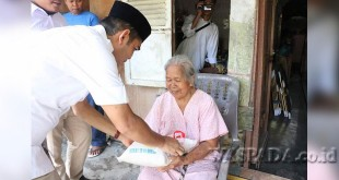 Wakil Ketua DPRD Medan, Ihwan Ritonga, membantu warga seputar posko Rumah Generasi di Kecamatan Medan Denai. (WOL Photo)