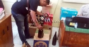 Petugas sedang melihat merek miras yang disita untuk dibawa ke Polrestabes Medan.(WOL Photo/gacok)
