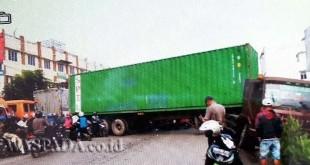 Kepala truk terperosok ke parit dan ekor melintang di badan jalan menimbulkan kemacatan arus lalin.(WOL Photo/gacok)
