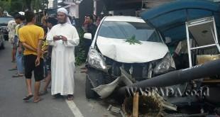Petugas URC Lantas Polsek Medan Sunggal berada di loksi kejadian mengamankan mobil Anvaza BK 6461 AFG yang menambrak pohon mangga, tiang listrik, stelling, dan sepeda motor lagi parkir. (WOL. Photo/Gacok)