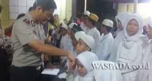 Kapolsek Medan Sunggal, Kompol Daniel Marinduri SIK SH MH, bersama Ketua Bhayakari membagi rezeki kepada anak yatim piatu.(WOL. Photo/Gacok)