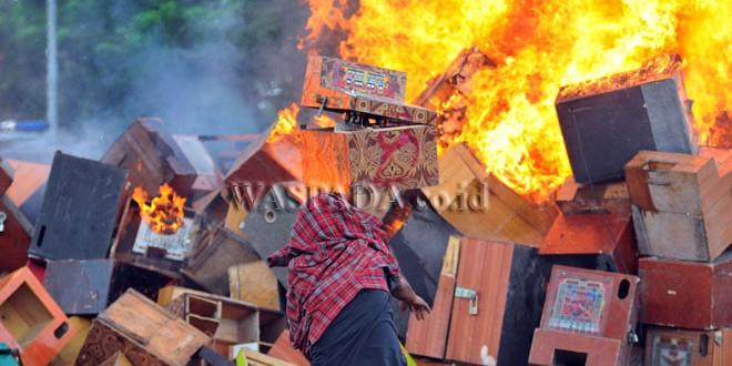 Seorang pria melemparkan mesin judi jackpot yang dimusnahkan, di Medan, Rabu (7/6). Sebanyak 670 mesin judi jackpot hasil barang bukti kasus perjudian dimusnahkan. (WOL Photo/Ega Ibra)