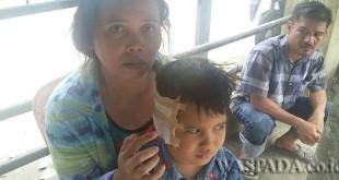 Bety Boru Situngkir menunjukkan luka pada bagian kepala anaknya akibat digigit anjing dan sementara Chandra Simbolon terlihat terduduk dan sedih melihat kondisi putrinya. (WOL. Photo/Gacok)