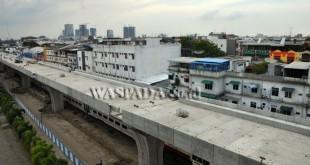 Kereta api melintas di bawah proyek pembangunan jalur layang kereta api, di Medan, Kamis (6/7). Pembangunan jalur layang kereta api dari Medan menuju Bandara Kualanamu sepanjang delapan kilometer, ditargetkan selesai akhir 2017. (WOL Photo/Ega Ibra)