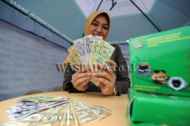 Petugas bank menunjukan mata uang Riyal di layanan penukaran uang Asrama Haji Embarkasi Medan, Senin (31/7). Layanan tersebut untuk memudahkan jamaah haji memperoleh Riyal untuk kebutuhan selama menunaikan ibadah haji di tanah suci. (WOL Photo/Ega Ibra)