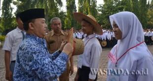 Kepsek SMKN 1 Percut Seituan, Drs Kasni MPd l, didampingi Wakasek bidang Kesiswaan, Sukirman SPd, menyematkan perlengkapan MPLS dari 752 siswa yang mengikuti MPLS.(WOL Photo/Ridin)