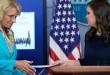 Sekertaris pers Gedung Putih menyerahkan sumbangan Presiden Trump. (Foto: AP)