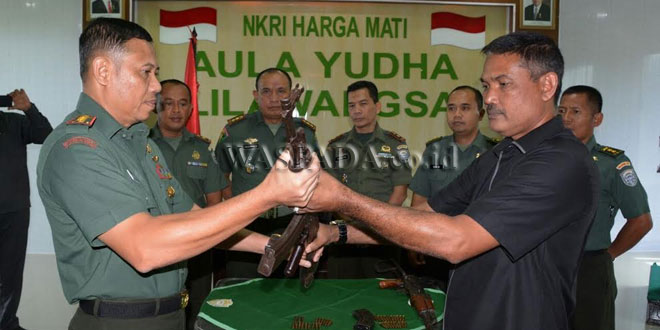 Komandan Tim Intelkam Korem 011/Lilawangsa, Kapten Inf Wahid, menyerahkan dua senjata AK kepada Danrem 011/Lilawangsa, Kolonel Inf Agus Firman Yusmono dari penyerahan dua warga di Aceh.(WOL Photo/Chairul sya'ban)
