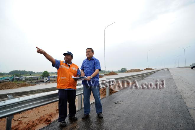 Pihak Jasa Marga, Jinto Sirait (kiri) menjelaskan perkembangan pembangunan jalan tol Kualanamu-Tebing Tinggi kepada Ketua Komite 2 DPD RI, Parlindungan Purba (kanan) saat meninjau proses pembangunan jalan tol, Deliserdang, Sumatera Utara, Sabtu (12/8). Tinjauan dilakukan untuk melihat perkembangan pembangunan jalan tol. (WOL Photo/Ega Ibra)